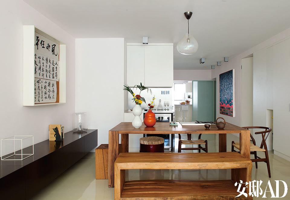 家不仅要容纳身体,更要妥帖包裹住心里的那份快意人生。餐桌左侧的墙面上安装了一整排储藏柜,外表看起来是几个大抽屉,内部却为主人的CD、文件等不同物件各自设计了储藏格,柜面上的小猫书挡来自新加坡。餐桌 前带有自然裂痕的长凳是由老樟木家具重新打造的,购于香港,餐桌后面的酒柜为德国Liebherr品牌。具有莹润珍珠光泽的半透明Bolla吊灯由意大利 FontanaArte出品,来自香港,Frank还为天花板设计了几只铝材外壳的射灯,夜晚它们会在地面上投射出有趣的光圈。墙上画作是黄姒的作品,来 自Hi小店(Hi Art Store)。