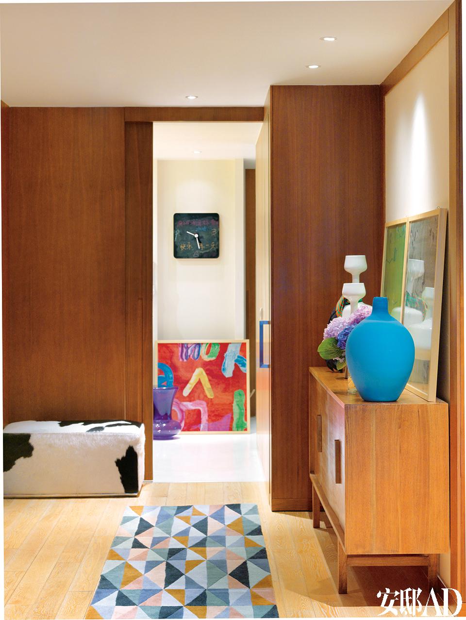 进门的玄关处以及与玄关相连的化妆室,紫色坐墩来自Kartell,旁边是毯言织造的装饰挂毯。