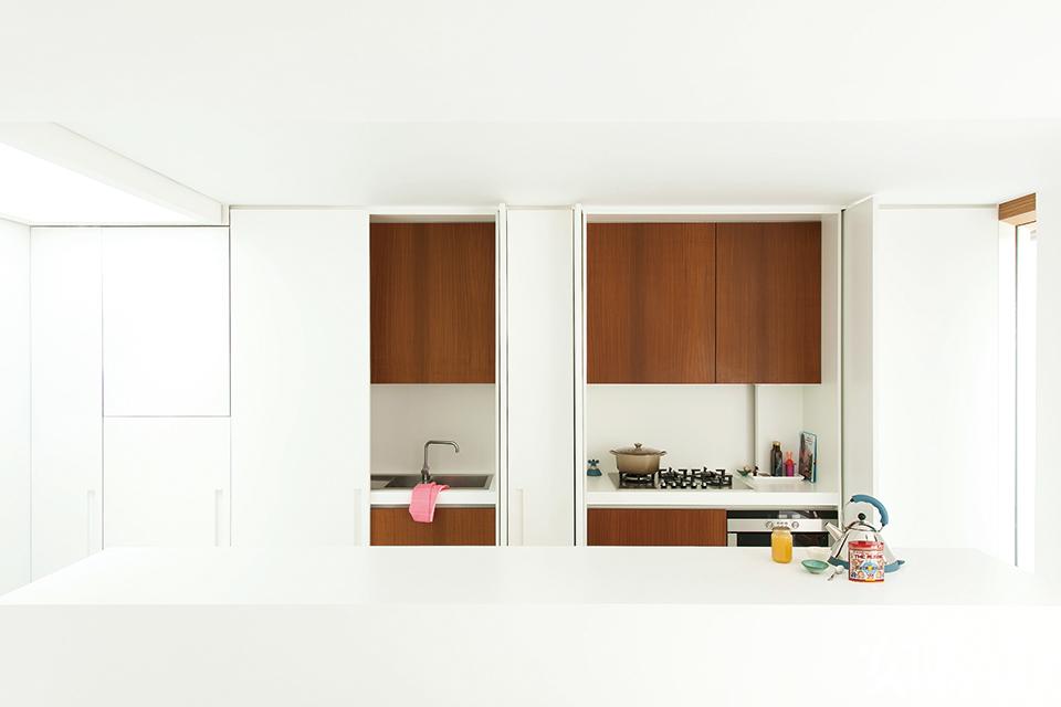从另一个角度看厨房空间,几幅卡通涂鸦式画作为这里增添了活泼的氛围。木质装饰则为这片简约的白色空间注入一丝暖意。 白色树脂地板将墙边木质装饰衬托得很 显眼,打开机关原来全都是储物装置!