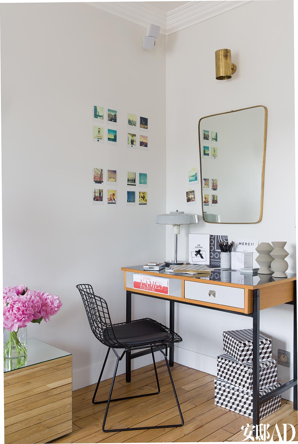 客厅一角的工作区,Bertoia Side Chair复古写字椅由Harry Bertoia在1952年设计,购自巴黎的Galerie Espaces 54,镜面的木柜来自Habitat。20世纪60年代丹麦风格的写字台是从一间过火后的废旧工厂里寻得的,被烧毁的表面如今重新贴上了塑料材质,购自巴 黎Nordik Market,桌上的两只丹麦花瓶同样来自那里,写字台下的黑白格盒子来自AM-PM。20世纪50年代的意式铜框镜来自巴黎Rue de Lille路上的一名古董商,墙上的宝丽来照片就是Christope在纽约的旅行记录。