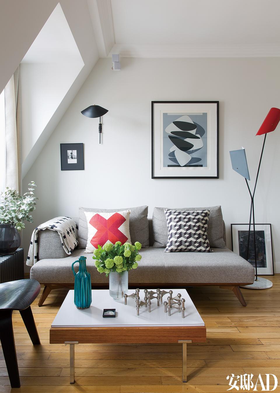 客厅中,挂画与灯饰搭配得天衣无缝。灰色布面的Sequoia沙发来自Steiner,沙发上的Santorin Rouge红十字架图案抱枕和Marrakech黑白立体图案抱枕都来自Rouge duRhin ,沙发扶手上的十字架图案盖毯来自Pia Wallén。墙上的大幅印刷艺术品由VictorVasarely创作,和它十分搭调的壁灯是Serge Mouille的设计。工业感的Stilnovo复古落地灯来自巴黎的跳蚤市场,它拥有大理石底座和喷漆的金属灯罩,它后面的地板上立着一幅来自Alessandro Moriconi的拼贴作品《Black Shadow》。前面的茶几是20世纪50年代用Formica、花梨木材质做成的镀铬底座咖啡桌,同样来自巴黎的跳蚤市场,湖蓝色水罐购自巴黎的一间艺廊,金属烛台是20世纪60年代的斯堪的纳维亚风格。