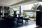 从镜面墙中反观餐厅,黑色的家具、地毯与明媚的户外景色形成强烈对比。