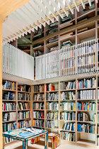 镜面天花板将空间向上延展,自然光从天窗照射进来,令整个空间更加明亮而有活力。图书馆隐藏在围墙内,当房门关闭时,俨然变成了一间书之密室,周遭的一切仿佛都已消失。天花板的镜面处理让这里变成了一片书的海洋,地上的桌椅均是Richard Woods的设计。