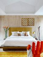 """风水师的建议也可以用聪明的方式完成:土黄、芥末黄可以替代金色,复古的铜镜也是""""补金""""的重点。风水师给Lilian的建议是多用""""金"""",如果不喜欢金色就用土黄等接近色来替代,金属物件就选铜。床后面清一色的木板墙,里面隔开的是一个步入式衣橱。"""