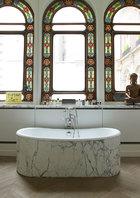 古老的彩色拱形玻璃窗搭配上现代化的浴室设备,传统与现代的交融让这个家显得格外与众不同。主浴室中选用了卡拉拉大理石的浴缸、窗台和橡木拼花地板,窗台上的黄底艺术摆件是来自Ben的Porno Star。