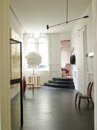 公寓的入口处保留了原有的木饰面墙,但都刷成了白色,如云朵般的白色轻型雕塑Innocent由Franz West创作于2011年,右侧是一把非洲部落椅。