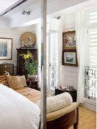 """卧室一角,其两窗中间的艺术品分别为廖继春的《野柳》(上)、陈进的《西雅图》(下),两位均为台湾第一代画家中之翘楚。长凳是叶裕清由旧金山家中搬回的 Daybed,床架为""""Ralph Lauren"""" 的四柱床。叶裕清共搜集近30张床架,其曼谷酒店里的所有床皆为自己用过。"""