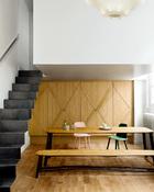 """整个厨房被隐藏在橡木门的后面,这种""""遮盖""""魔法术让日常生活的杂乱场景顷刻隐形。橡木门闭合起来,这里就是一个完整的餐厅。由Valentin Loellmann设计的长桌和 """"Fall/Winter""""长凳(来自Gosserez工作室)拥有多重用途。旁边还有出自David Geckeler 的""""Nerd""""椅子(Muuto au Bon Marché),桌上还放着来自CFOC的水杯。"""