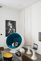房间一角摆放着由Eero Aarnio设计的蓝白色玻璃纤维球形椅(Fiber Ball Chair),散落的带有黑白图片的几只小凳子是摄影师和设计师Maurice Renoma对Tam Tam凳的再设计。