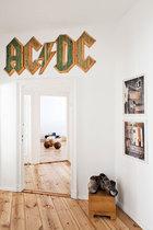 """门上的""""ACDC""""字样木质装饰是Rene Lück的作品,一侧墙面上挂着两幅Johannes Schwarz的摄影作品。"""
