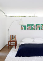 墙壁与天花之间留出的一小条玻璃面,不仅纳入美丽的自然光,让绿意也渗透进来。主卧室里的床来自B&B Italia,落地灯是Tolomeo Mega Terra来自Artemide,椅子则是复古的丹麦设计。