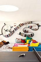 这款著名的书架,在这个家里被拼出最艺术的线条,周边点缀的小相框,更是独出心裁。在孩子们的游戏室里,一个炮眼天窗将自然光从厨房带进地下室。这里蜿蜒的Bookworm书架是Ron Arad为Kartell设计的。Eames夫妇为Vitra设计的Rocking Chair和Roche Bobois的麻将(Mah Jong)大沙发为居室增色不少。