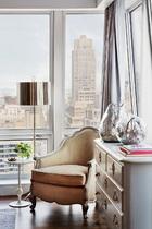 主卧室一角,窗外曼哈顿的街景仿佛触手可及。柜子为Coté France,美人椅来自Oly Studio,落地灯来自Robert Abby。