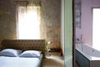 """""""我很害怕为物所役,特别是成为装饰的俘虏。一切富饶、丰收、繁多的意象都会让我精神错乱,拥有得越少我才越觉得安全。""""伊丽莎的卧室高雅而简洁,床头的装饰和窗帘选用了相同的布料。通过绿色玻璃门可以进入浴室。"""