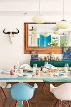 """餐桌采用了回收的船板木,女主人花了4个星期请工人做成,再为不同木块涂上各异的浅淡色彩,搭""""配寿司女王""""的斑斓寿司,再合适不过!餐桌上方悬挂着三盏1963年制造的吊灯,主人从巴黎的Marche aux Puces觅得,原本是一家酒店大堂的吊灯。餐桌上的Artoni Arte Murano彩色玻璃杯来自Lane Crawford。"""