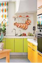 厨房中选用了柠檬和橙色的橱柜,不同型号的铜质平底锅排列出美食的律动。