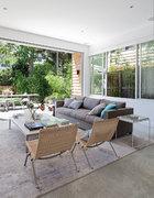 从另一个角度看起居室,目光能直接穿过露台到达后花园里。藤编休闲椅来自PK22,地毯是在Trendy Rugs定制的手工丝线地毯。