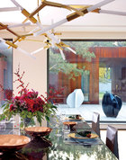 """坐在餐桌旁向外望去,正对着与新加盖的客厅围合而成的院落,窗外的雕塑和松枝都成为佐餐良伴。这张长长的西式餐桌是经由任小勇的""""死谏""""才得以保留的。而王太则依据自己的生活经验,将它从最初的白色换成了如今的深色。枝形吊灯来自Roll & Hill, 铜餐具来自Tom Dixon,餐具来自L'Objet,以上物品均购于家天地。"""