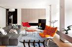 位于一层的另一个小客厅里,设计感十足的家具与艺术品成为主角。红色与橘色座椅来自B&B Italia,灰色沙发同样来自B&B Italia,名为Tufty-Too,白色落地灯来自Roll & Hill,架子上的枝形烛台来自Tom Dixon,以上物品均购于家天地。