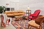 """二楼夹层上的客厅中,白色的皮质激光镂空屏风为Poltrona Frau品牌,来自北京居然之家,咖啡色的Maralunga沙发是设计师Vico Magistretti在1973年为Cassina品牌设计的原版产品,茶几的木料据说有千年历史,它是来自Ben父亲的馈赠,茶几上的渐变色矮花瓶来 自Spin北京丽都店。近处的座椅由Ben设计于2008年,它是用一块称作""""ReBoard""""的蜂窝纸板制成的,可以喷涂任何图案。右下角的木质单椅也 是Ben的得意收藏,它是Hans Wegner在1949年设计的Shell椅的早期样品,现在已经很罕见,这是妻子Alex在Ben 40周岁生日时送给他的礼物。客厅中混合了古董、大师名作和Ben自己的设计创意,更有一抹亮丽的""""中国红""""。"""
