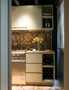 """厨房中配置了被称为""""计划美食家""""的法国Lacanche炉具,墙面和地面都铺装了来自Uzes的普罗旺斯风格XVIeme瓷砖。"""