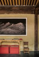 """这或许是当前北京最好的设计酒店,Juan Van Wassenhove以及他的合伙人林凡、周理贤用打造自己的家一般的力道,悉心修复古建,挑选设计家具和艺术品, 为每一个角落播撒下光阴的魅力。一幅由瑞士女摄影师Irene Kung创作的摄影作品《长城》挂在酒店大 堂中,画面非常震撼。她在2011年来中国时拍摄了多幅作品,包括《天坛》以及对这间酒店本身的摄影。木质条案是酒店的工作团队自主设计制造的,这种松木经碳化后拉丝而成的板材同样应用在酒店中的很多家具上。条案下的两只红漆提盒来自""""上下""""。"""
