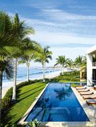 辛迪家的泳池与碧海蓝天自然融为一体,泳池边的躺椅是Jasper定制的柚木椅。