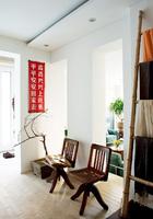 主人Arnd从工地上搬回来的大标语喜庆地挂在门厅中,预示着一天的好心情。虬枝挺立的银杏树盆景是房子前主人的馈赠,一旁的两把源自20世纪初老上海的木质办公椅是Arnd 10年前从北京高碑店淘来的古董,颇惹人喜爱,他甚至还照这个式样用不锈钢和黄铜仿制了几把。