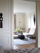 """前客厅中,高靠背沙发由Thomas自己的工作室出品,沙发前的黑色古董木茶几来自中国,由Marc Bankowsky设计的青铜小凳上包着ScalamandreFabrics的天鹅绒面料。墙上的青铜壁灯由巴黎的FelixAgostini设计,黑色青铜墙面雕塑则是美国艺术家Lisa Scheer的作品。""""我希望公寓整体上是法式风格,但在装饰和设计细节上却走我熟悉的美国路线。"""""""