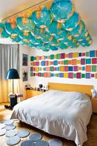 """天花板上的地球仪方阵和墙面上的粉彩""""相框""""都是艺术名品,地面上的圆形地毯,更与地球仪做着俏皮呼应。卧室的天花板上吊着AngeLeccia的地球仪方阵,灰色小地毯的组合来自Bouroullec兄弟,Bells落地灯也是他们的作品。墙上的 Surrogate装饰由AllanMcCollum设计,两幅照片的作者是Xavier Veilhan。"""
