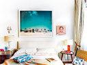 """卧室里挂着Yiorgos Kordakis的摄影作品。照片两边,左边小架子上放着的是Guillermo Mora的作品Packs V,右边是Angélica Dass的作品系列Humanae中Montse的肖像照。左侧的床头桌来自Gastón Y Daniela,上面摆放着A. R. Martineau的石膏台灯。右侧的床头桌来自LaRecova,上面摆放着一盏树脂台灯。前面是一张在EL 8购买的绳椅,上面放着Julia Martínez设计的靠垫,购买于Petit Point。床单来自Joie,搭毯来自CH Carolina Herrera。""""你可以踩碎花朵,但不能阻挡春天。""""Montse和她的杂志都不是一日之花。"""