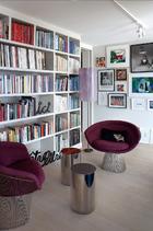 """客厅里,书柜一角,两个镜面抛光不锈钢独脚小圆桌出自Martin Székély,购于巴黎Kréo画廊,在书柜和地面上,出自Ben Vautier的三个放在有机玻璃底座上面的抛光金属作品:""""是""""(être)、自由(libre)和此处(ici),三个单词可以自由组合,表达不同的 意思。在靠里面的墙面上,一系列作品组合:Carrie MaeWeems关于黑人境遇的摄影作品、Roy Lichtenstein的石版画、Boetti的两幅作品,尤其还有Gavin Turk的一幅作品,与Boetti的作品颇为相似。客厅内最美丽的艺术品,与客厅外莱蒙湖畔以及阿尔卑斯山变幻多端的景色相呼应,相得益彰。"""