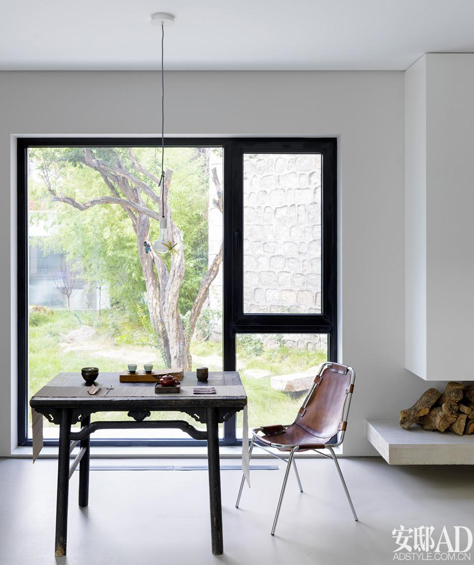 窗邊設有品茶區,置有山西的大漆木桌、藥柜、兩張小板凳,與Charlotte Perriand的皮椅相配。 一邊是要保證充分宜居,完全理性思考房子的自我調節能力、家庭活動等需求,一邊又要兼顧美感,這是設計過程中頻發沖突的關鍵所在然而最終兩位建筑師發現,答案并非哪一方的妥協,真誠面對自身需求始終是本質,出自真誠的設計才會引向美。因此,這個家內沒有任一部分的設計是經由形式、風格語言而被刻意凸顯的,一切輕盈、利落。屋內壁面一律以白墻與水泥自流平鋪設,其中幾面經由真石漆粗糙處理的墻是兩位建筑師向他們的偶像、