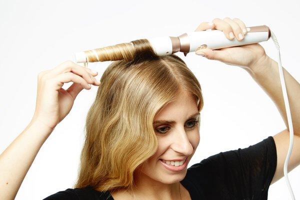 挑出一缕发丝缠绕在卷发棒上,发根靠近卷发棒末端比较粗的位置图片