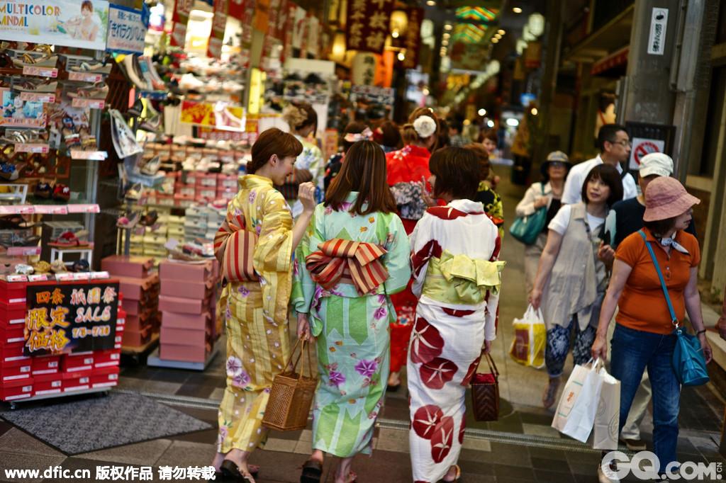 """锦市场在1615年作为鱼市场开张,至今已经有400年历史了,这里被称为是""""京都的厨房"""",各种美食纪念品应有尽有。当地时间2013年7月18日,日本京都,亚洲游客穿着和服逛锦市场。"""
